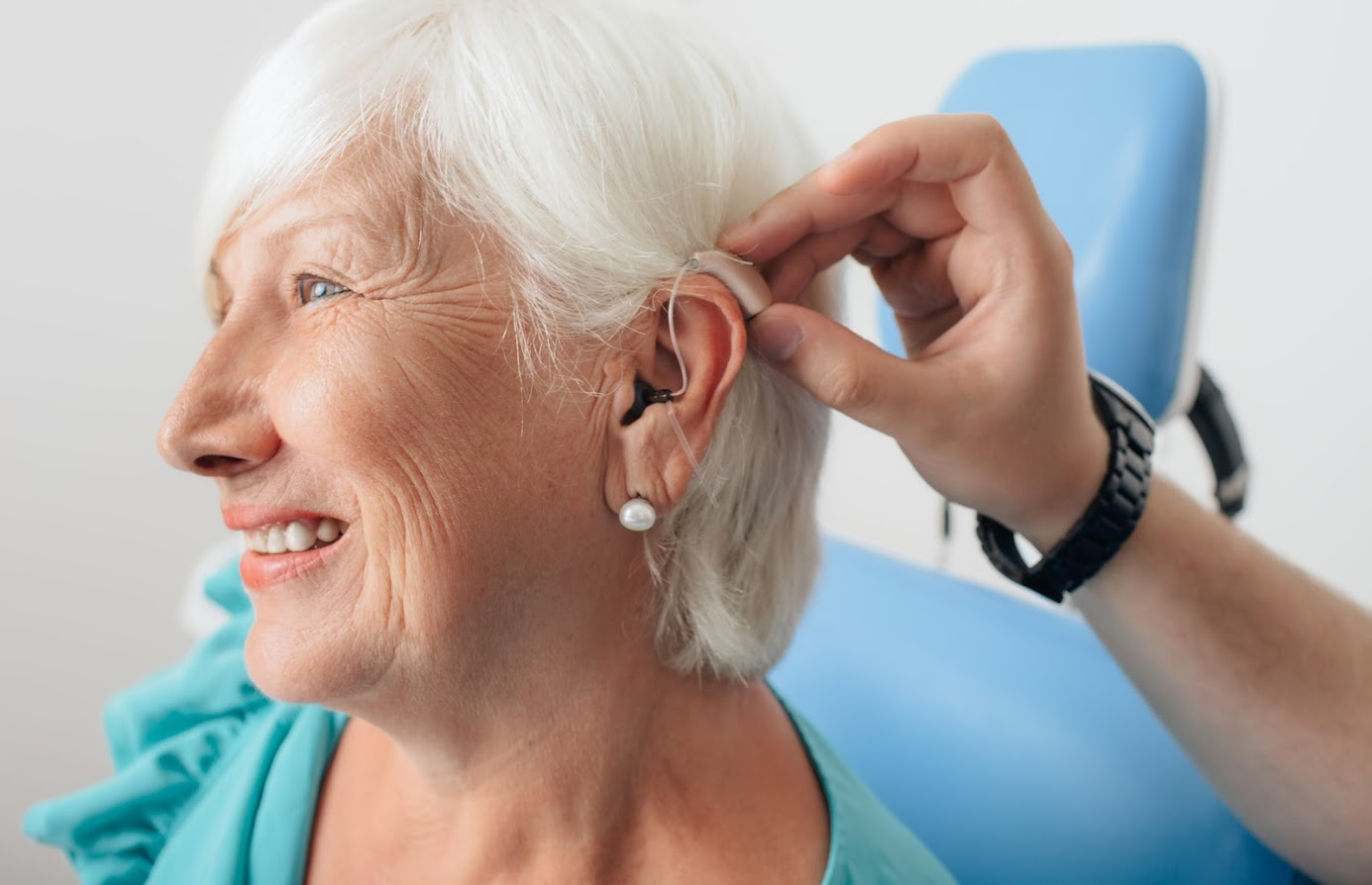 A hearing aid being placed on an elderly woman