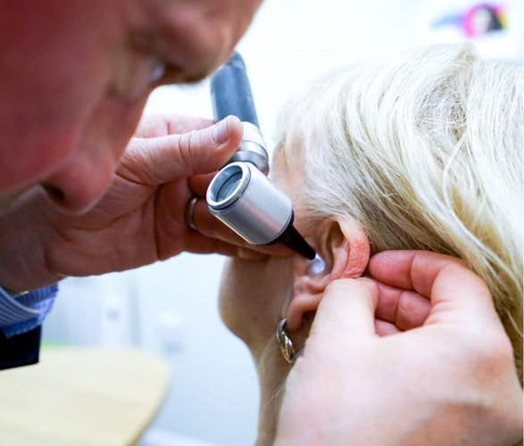 ear doctor examining patient with otoscope