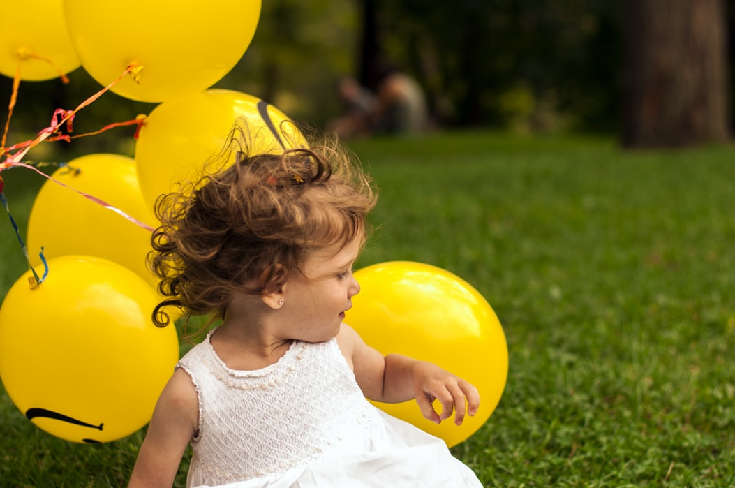 A little girl sitting in front of yellow balloons