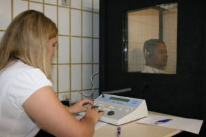 Audiologist performing a hearing test with a patient