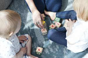 A woman and two children playing with wooden blocks