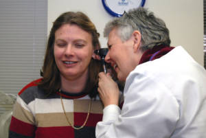 A patient having her ear examined by a hearing professional