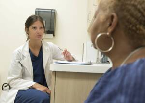 A hearing professional speaking to a patient