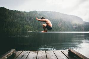 A person jumping off a dock into a body of water