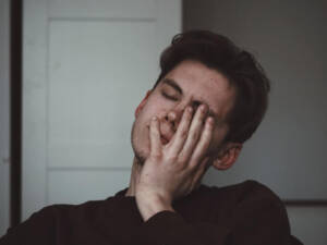 Man rubbing face due to tinnitus condition