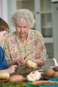 An older woman cutting a potato